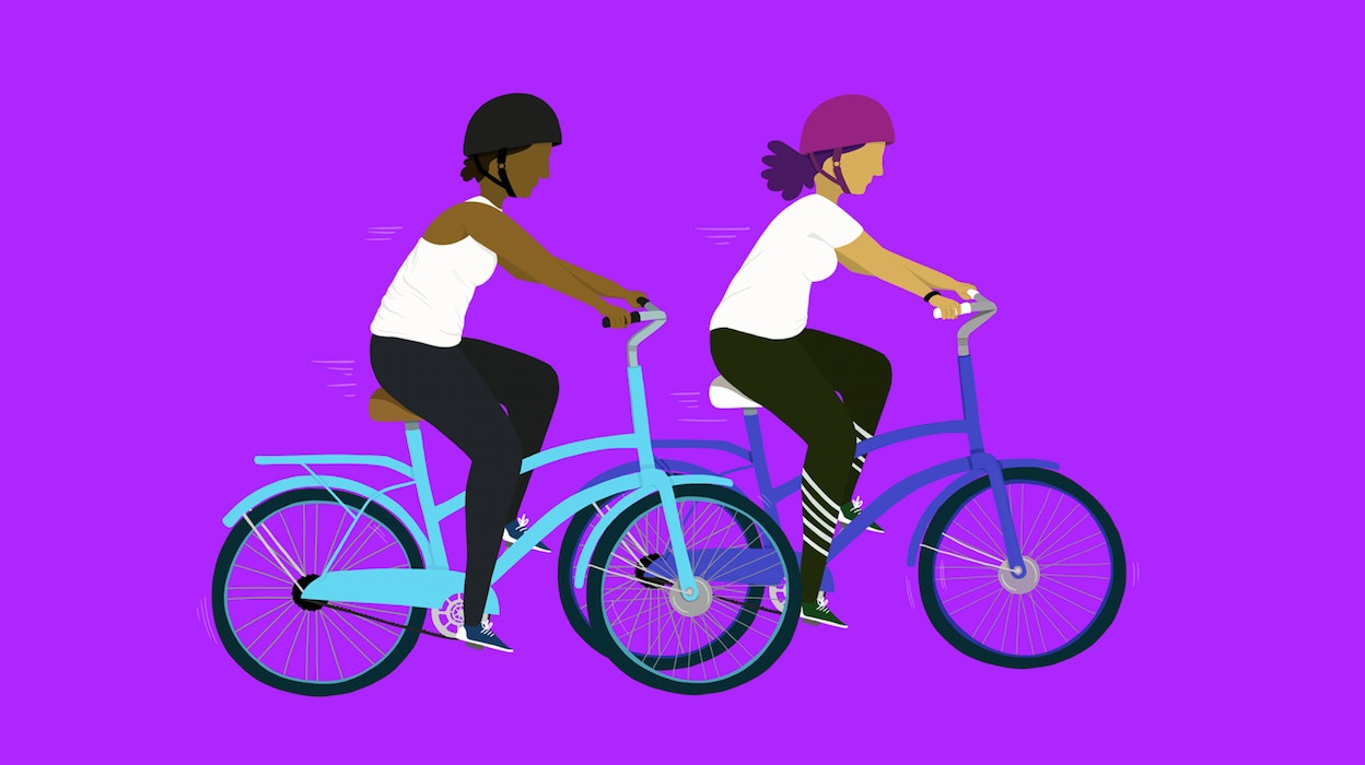 Two people riding bicycles together