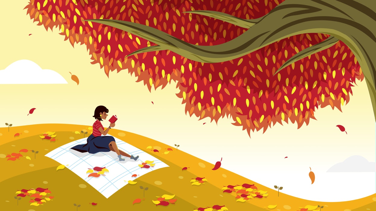 Woman reading a book next to an autumnal tree with falling leaves