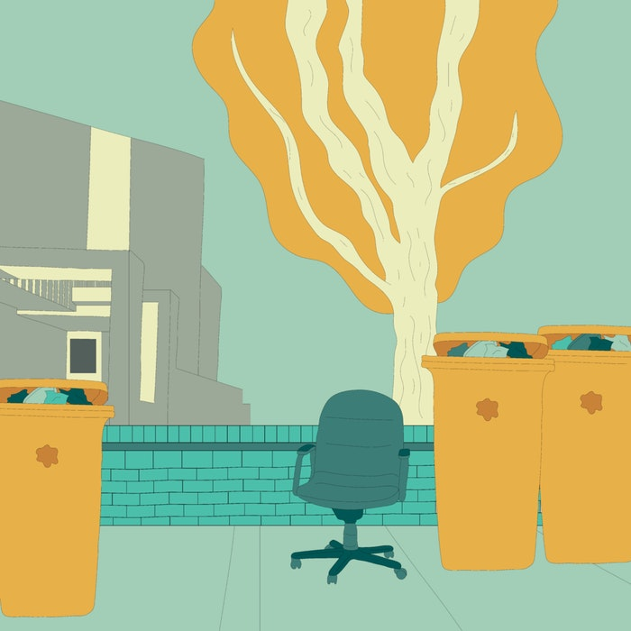 Garbage bins full of rubbish and discarded office furniture