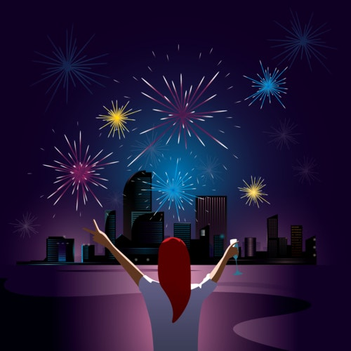 Woman watching fireworks over a city skyline