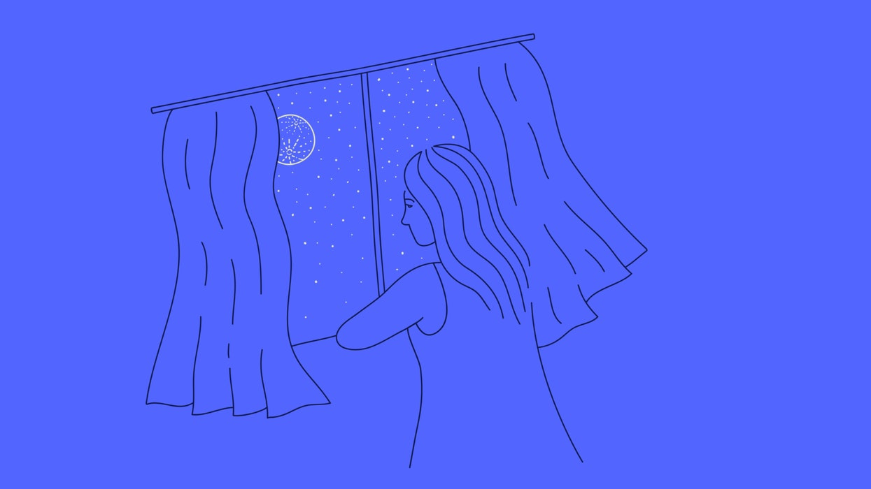 Woman staring out the window, looking at the night sky