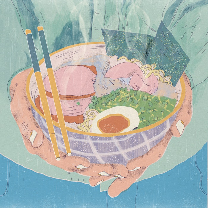Hands holding a bowl of ramen