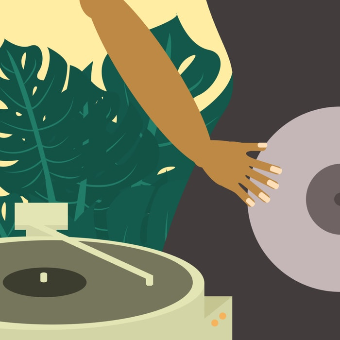 Person holding a vinyl record next to a record player
