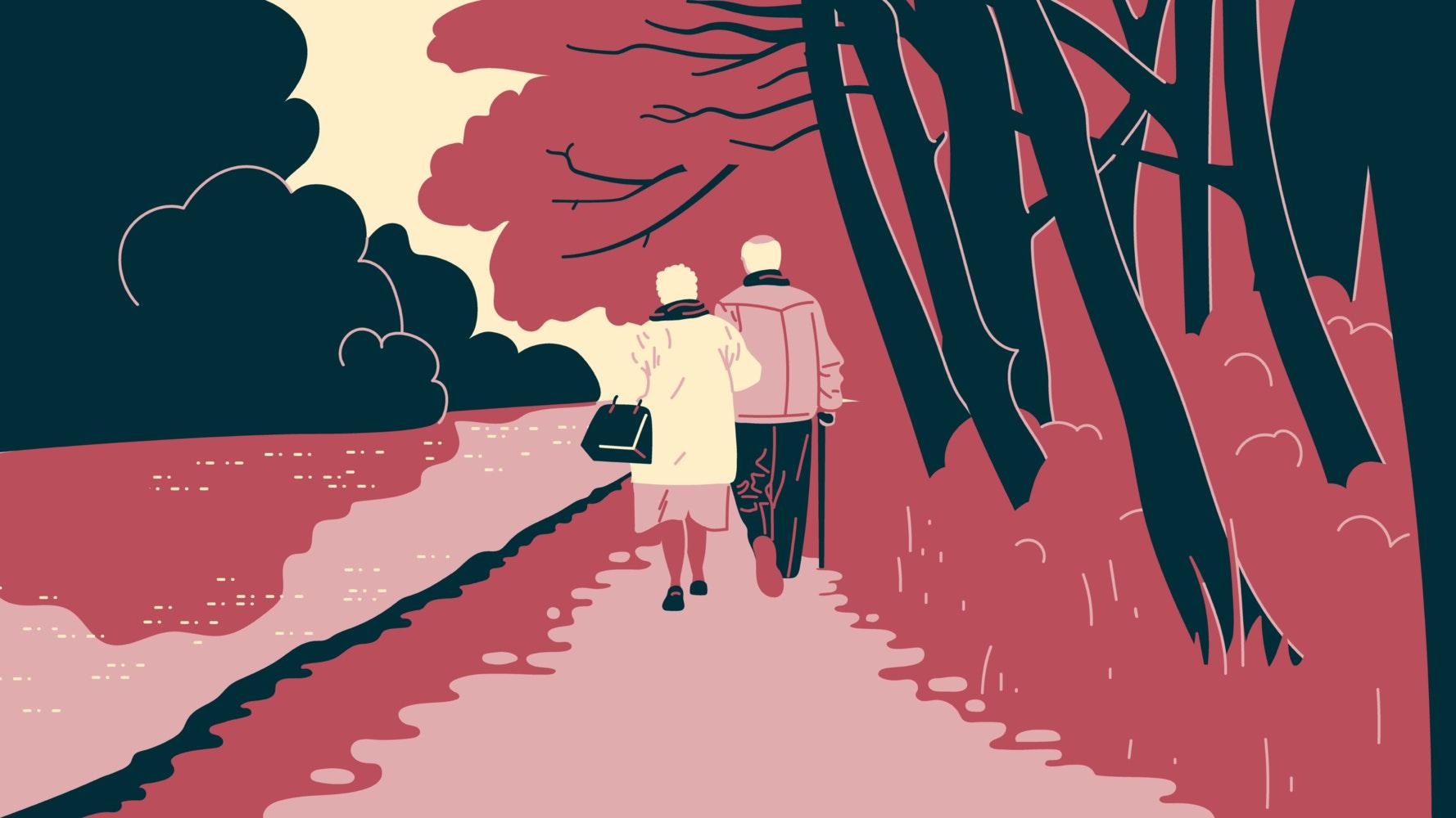 Elderly couple walking arm in arm through a park