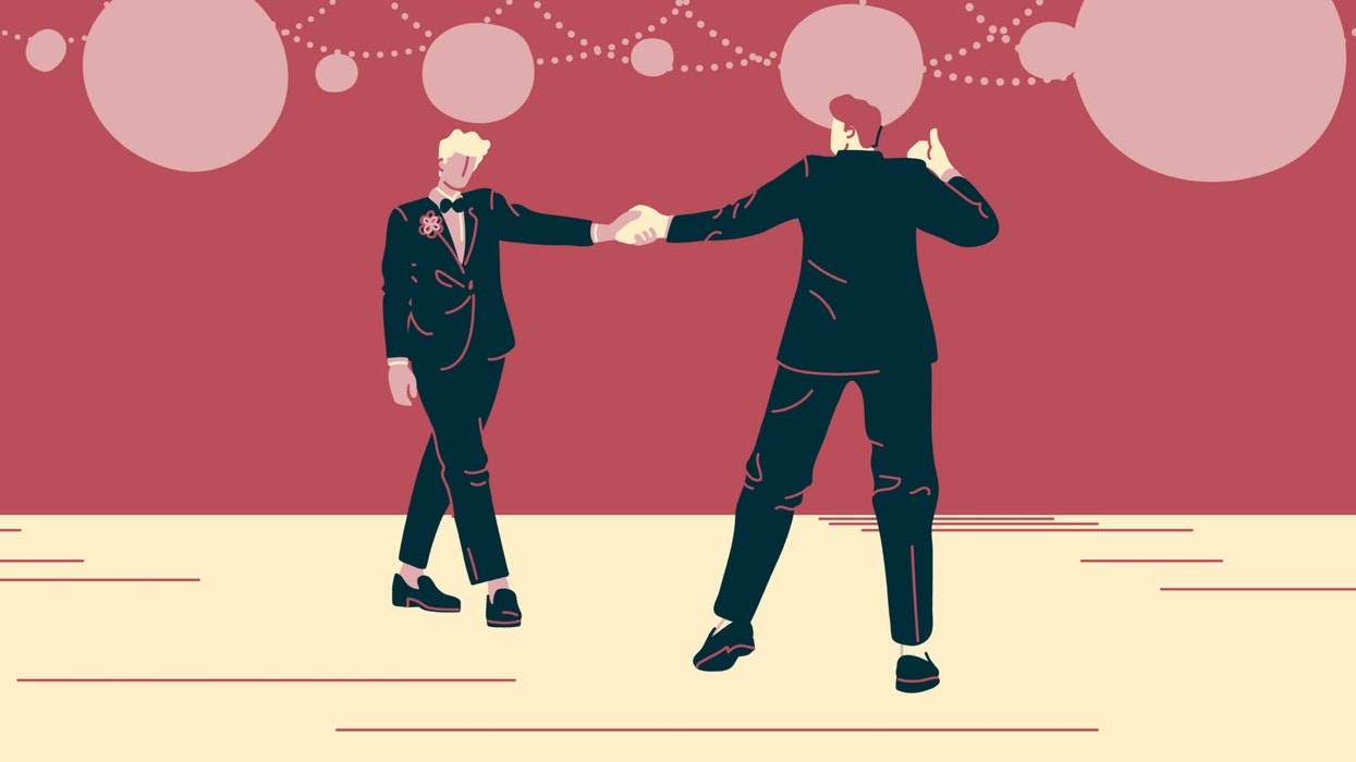 Couple in suits dancing at a wedding