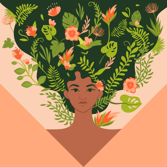 Strong woman with flowers and plants weaving through her hair