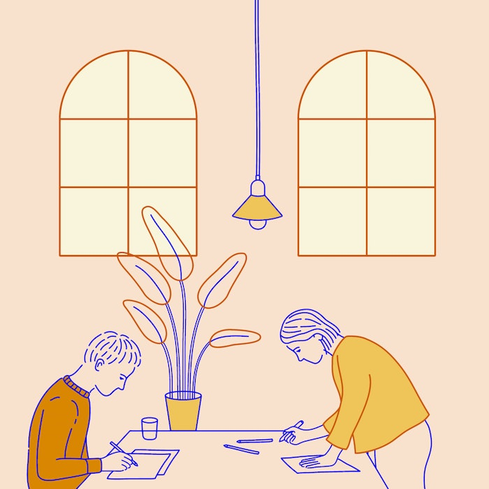 Two artists working at a shared desk