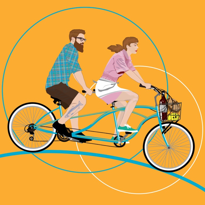Couple on a tandem bicycle with wine, bread, and cheese in the front basket