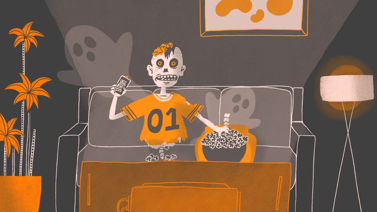 Halloween zombie sitting on a couch eating popcorn and watching TV