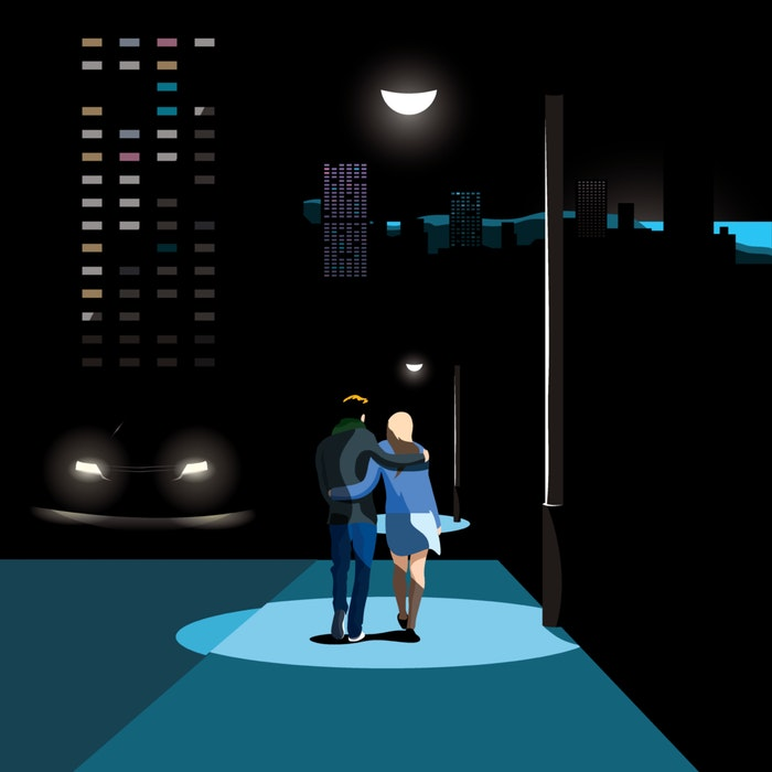 Couple walking arm in arm, illuminated by a street light and the moon