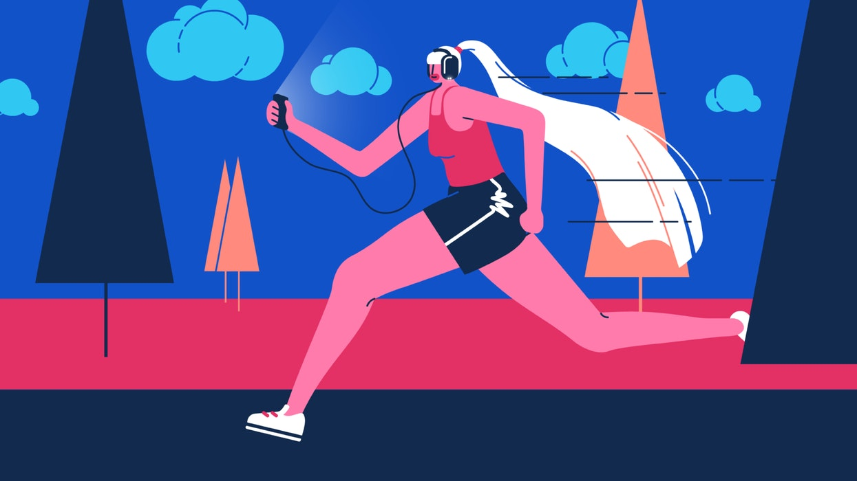 Woman running while wearing headphones and holding a mobile phone