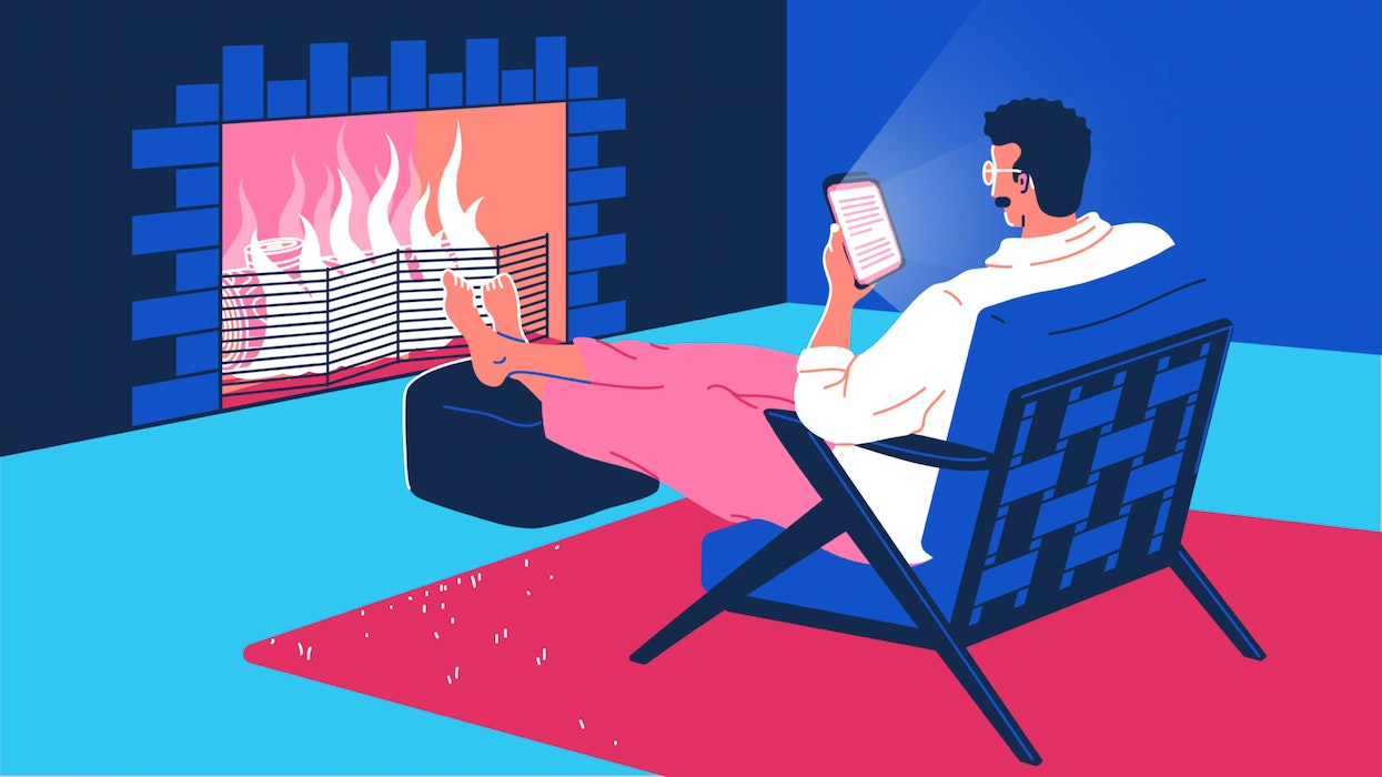 Man sitting in front of a fire, reading from a tablet