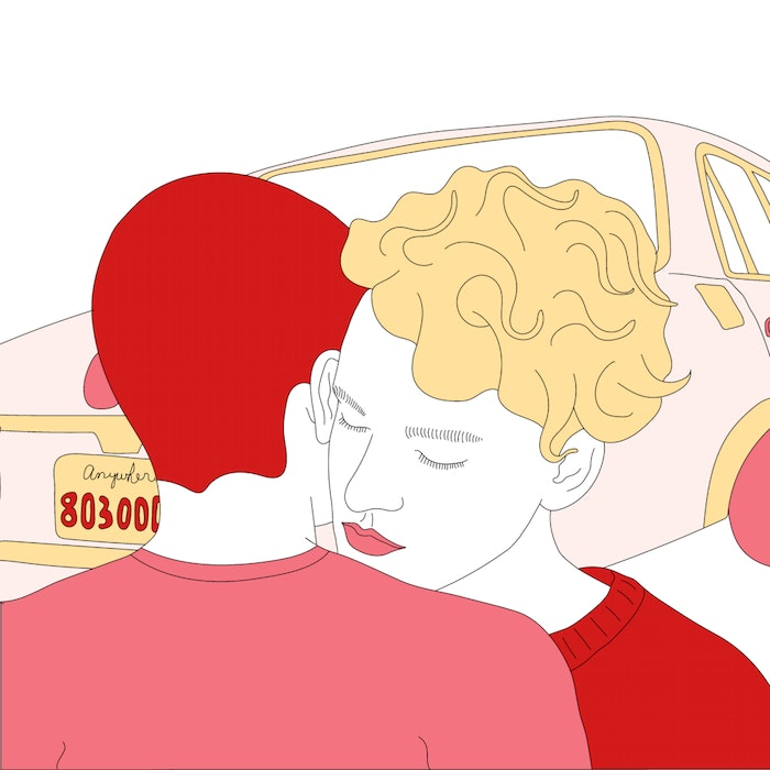 Couple embracing in front of a car