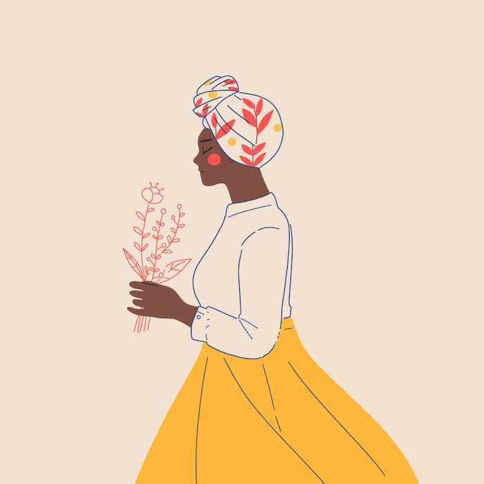 Woman wearing a bright headscarf and carrying flowers