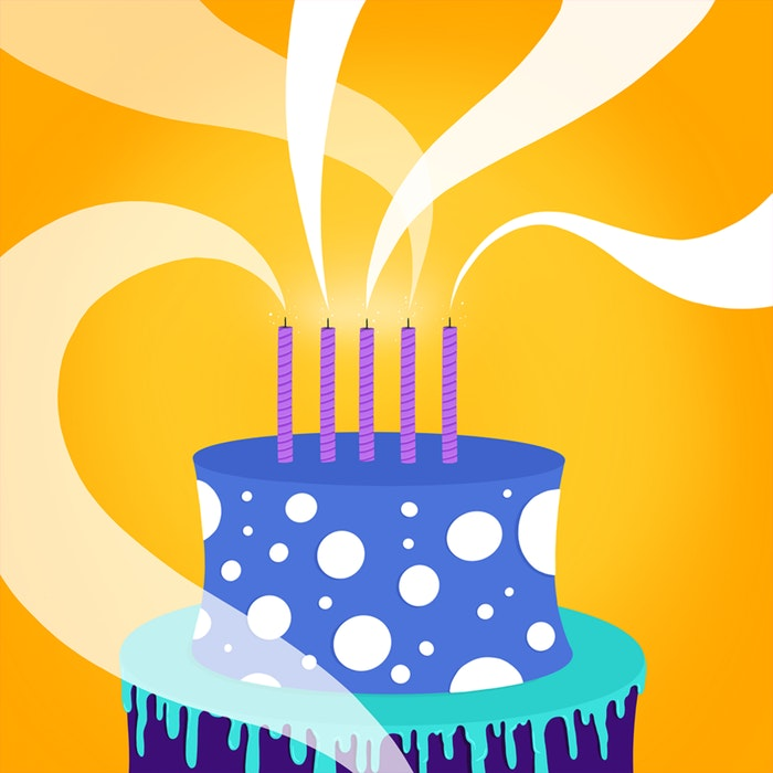 Tiered birthday cake with five lit candles