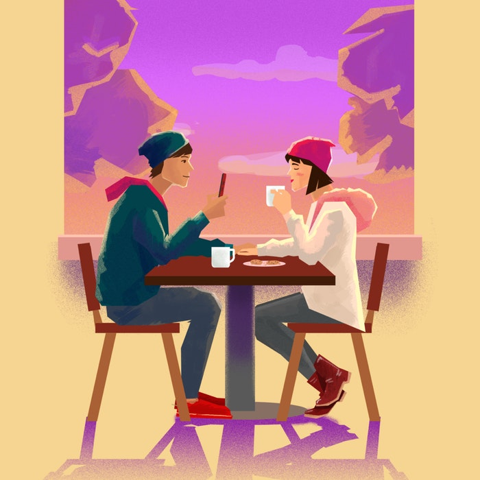 Couple taking a photo on a mobile phone while sharing food and drinks at an outdoor cafe