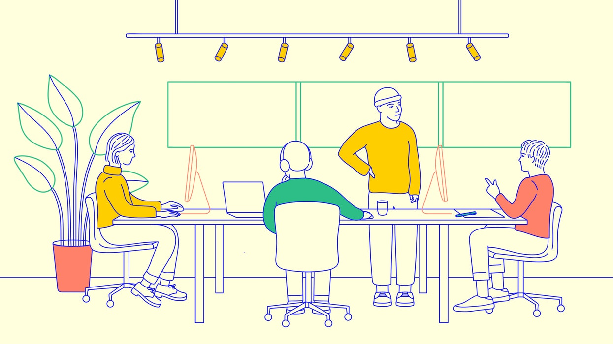 Four people working together at a shared desk in an open plan office