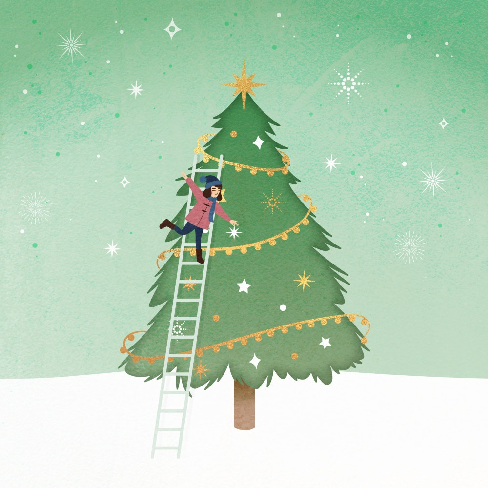 Girl decorating a Christmas tree in the snow