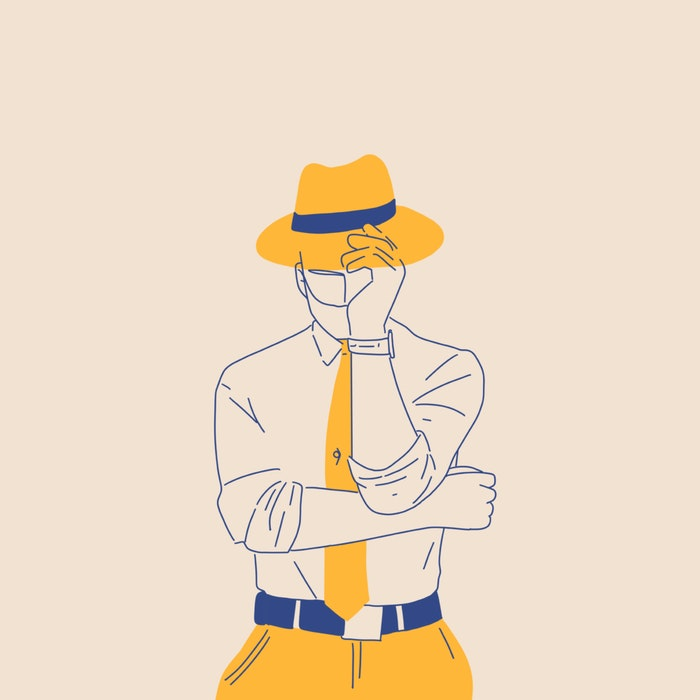 Man holding the brim of a yellow fedora that covers his face