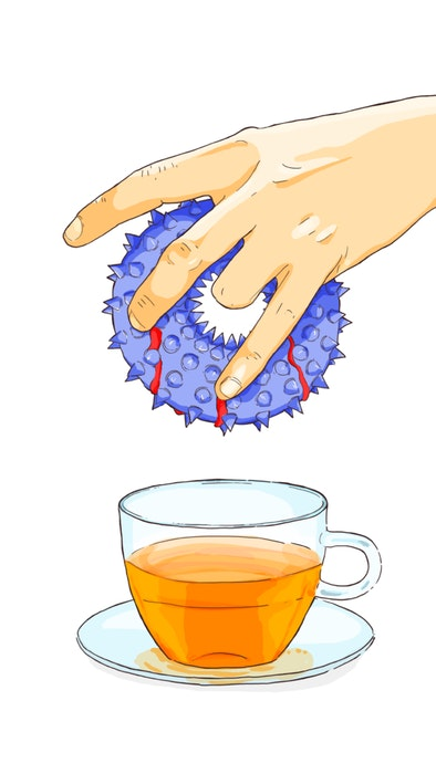 Person dunking a donut into a cup of tea