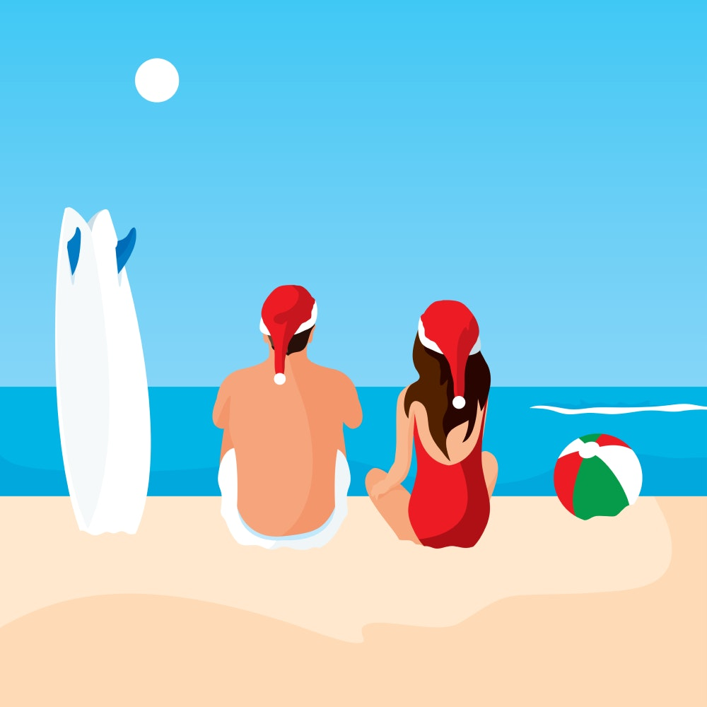 Surfers wearing Santa hats at the beach on a sunny day