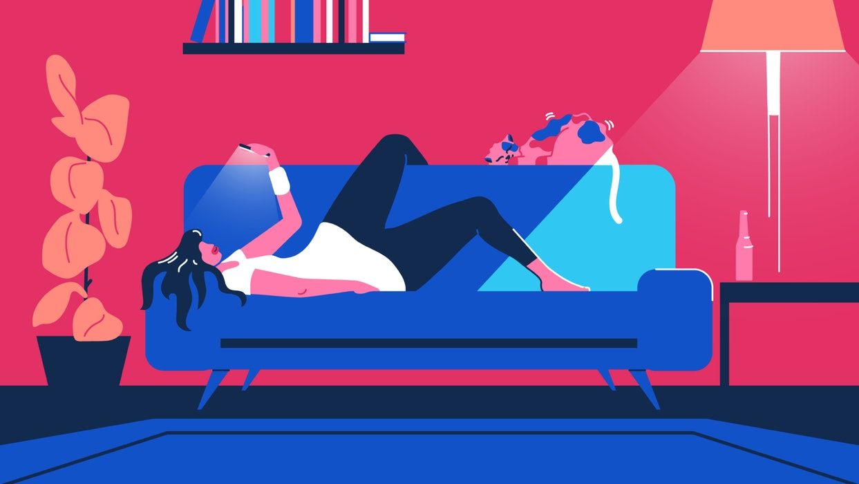 Woman lying on a couch looking at her mobile phone