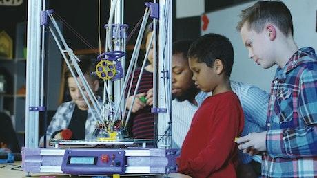 3-D printer in action in kids classroom