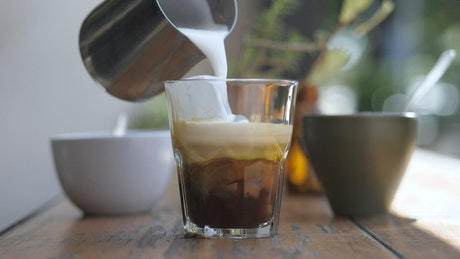 A barista preparing coffee with milk and ice