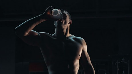 A bodybuilder is drinking water