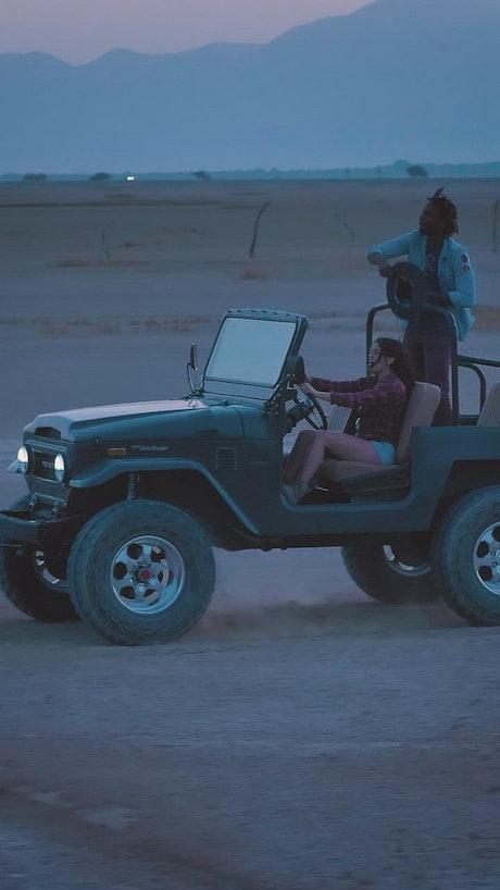 A boy and a girl enjoying a road trip through the desert