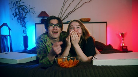 A boy and a girl laughing while watching television