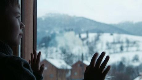 A boy draws imaginary shapes on window