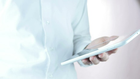 A businessman holding a tablet does the thumbs-up sign