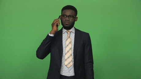 A businessman in a suit talking on the phone