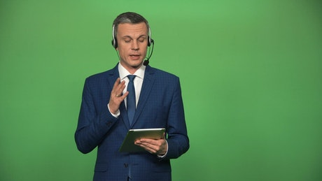 A businessman with a headset and a tablet talking