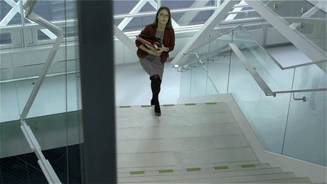 A businesswoman going upstairs in a hurry