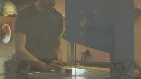 A carpenter using a sawing machine