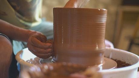A ceramic artist making a vase