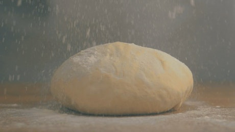 A chef covering dough with flour
