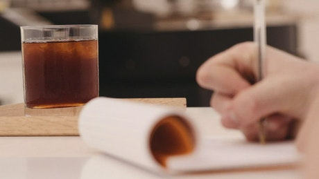 A coffee drinker taking notes