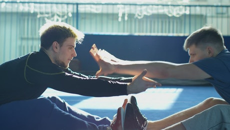 A couple of athletes stretching each other