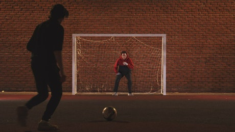 A couple of friends playing football at night