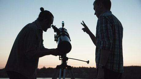 A couple of man using a telescope at dawn