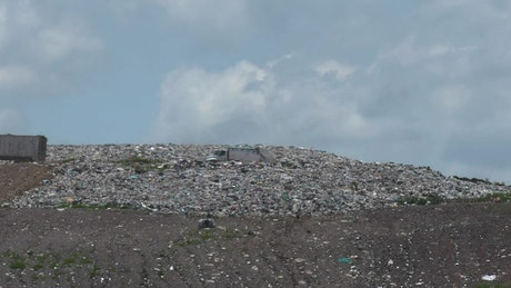 A couple of trucks crossing a hill in a dump