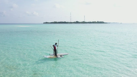 A couple paddling on boards on turquoise sea