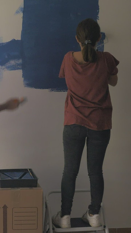A couple painting a wall blue