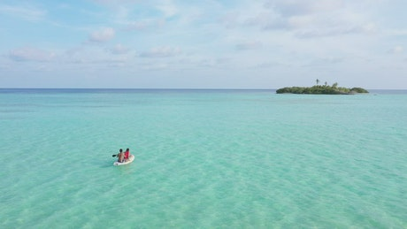 A couple seated on a paddle board in the sea