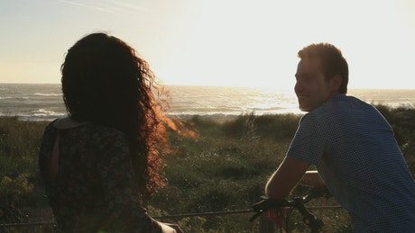 A couple watching the sunset at the sea