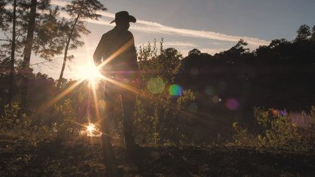 A cowboy standing in a field at sunset