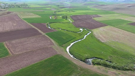 A curvy river through agricultural fields in the valley